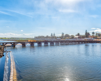 CAPE TOWN, SOUTH AFRICA, AUGUST 14, 2018: The lagoon in the Diep River and historic wooden bridge in Milnerton. Vehicles are visible